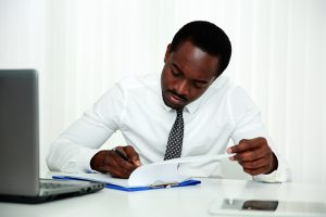 business man signing document in office